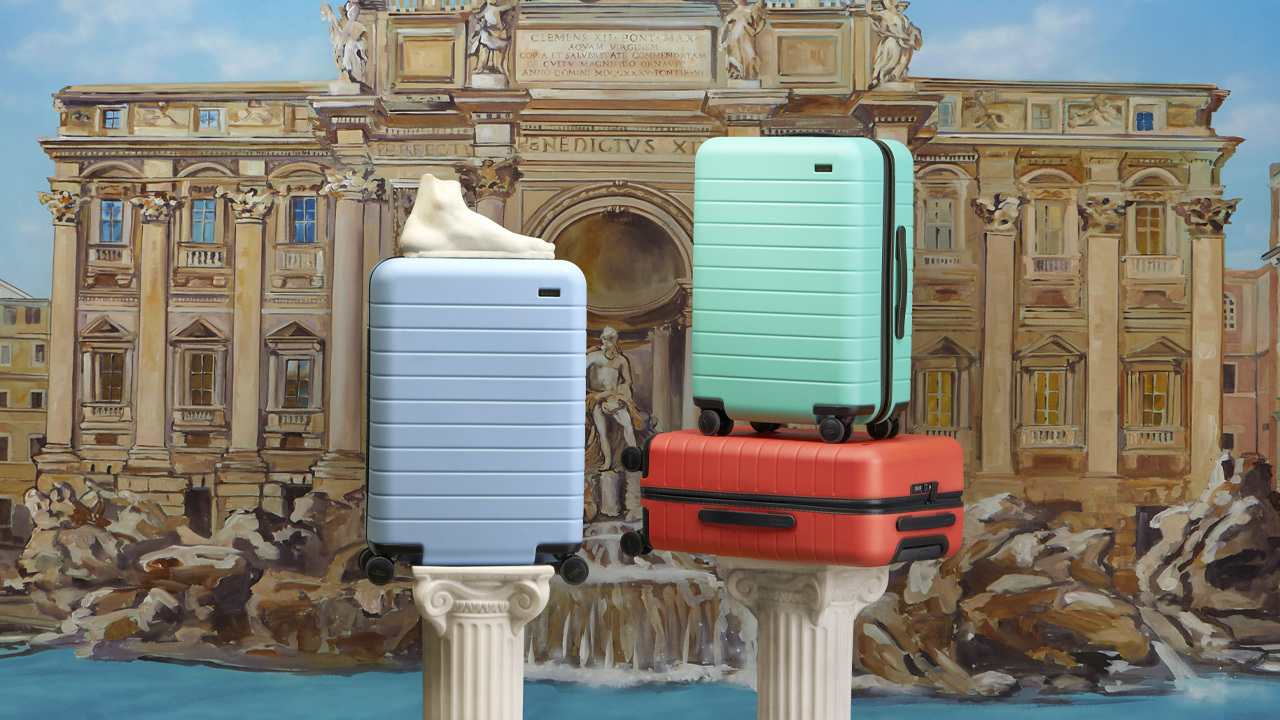 serena williams away collection: Three suitcases from the Away x Serena Williams collection are posed in front of a drawing of the Trevi Fountain in Rome